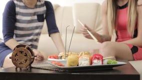Deux amies parlant pendant le dîner au restaurant, mangeant roule avec des baguettes clips vidéos