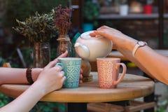 Deux amies parlent et boivent du thé en café, dehors Photos stock