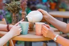 Deux amies parlent et boivent du thé en café, dehors Image stock