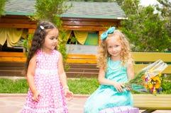 Deux amies Petits enfants adorables avec le bouquet des fleurs sur le joyeux anniversaire Gosse en stationnement Photo stock