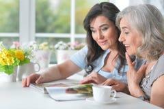 Deux amies pluses âgé lisent un magazine Image stock