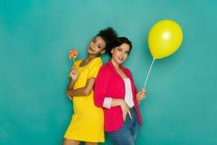 Deux amies posant au fond de studio d'azur Photographie stock