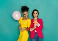 Deux amies posant au fond de studio d'azur Photo stock