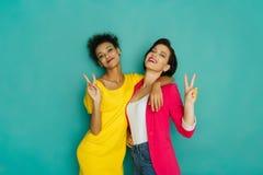 Deux amies posant ayant l'amusement au fond de studio de turquoise Photo stock