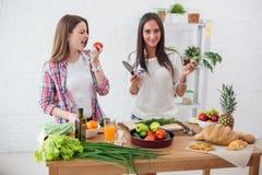 Deux amies préparant le dîner dans un concept de cuisine faisant cuire, mode de vie culinaire et sain Image libre de droits