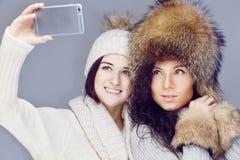 Deux amies prenant la photo sur le smartphone photo stock