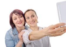 Deux amies prenant le selfie avec le comprimé numérique Photographie stock