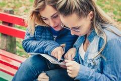 Deux amies recherchant dans une carte dehors Photographie stock libre de droits