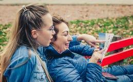 Deux amies recherchant dans une carte dehors Image stock