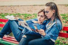 Deux amies recherchant dans une carte dehors Photos libres de droits