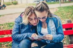 Deux amies recherchant dans une carte dehors Photo stock