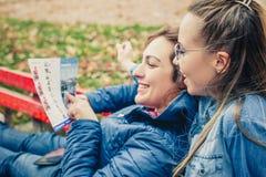 Deux amies recherchant dans une carte dehors Photographie stock