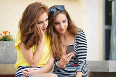 Deux amies regardant des photos au téléphone portable Photographie stock libre de droits