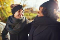 Deux amies regardant l'un l'autre et le sourire Photo stock