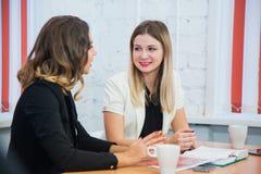 Deux amies reposent ensemble l'entretien discutent le sourire Images stock