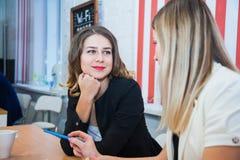 Deux amies reposent ensemble l'entretien discutent le sourire Photos libres de droits