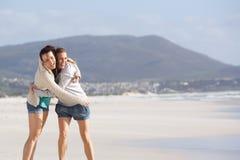 Deux amies riantes à la plage Image stock