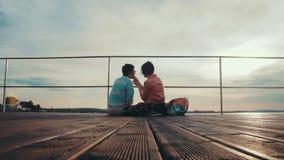Deux amies s'alimentant détendant par l'étang se reposant au bord d'un pilier en bois Jour d'été joyeux de clips vidéos