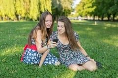 Deux amies s'asseyant dans un dégagement ensemble de l'utilisation un smartphone Photographie stock