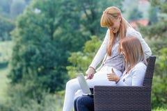 Deux amies s'asseyant dehors Photographie stock libre de droits
