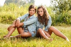Deux amies s'asseyant sur l'herbe Photographie stock libre de droits