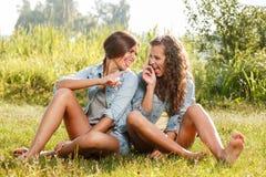 Deux amies s'asseyant sur l'herbe Images libres de droits