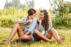 Deux amies s'asseyant sur l'herbe Photo stock