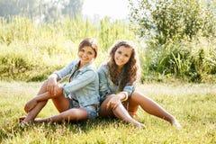 Deux amies s'asseyant sur l'herbe Photos libres de droits