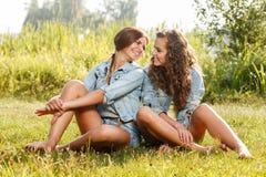 Deux amies s'asseyant sur l'herbe Image stock