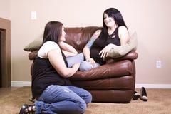 Deux amies s'asseyant sur le divan Photographie stock