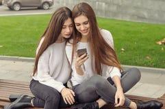 Deux amies s'asseyent sur le banc et observant décrit I Photo stock