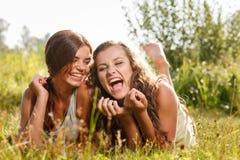 Deux amies se couchant sur l'herbe Photographie stock
