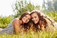 Deux amies se couchant sur l'herbe Images stock