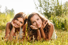Deux amies se couchant sur l'herbe Photo stock