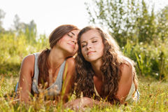 Deux amies se couchant sur l'herbe Image stock