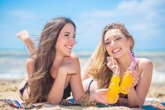 Deux amies se reposant sur la plage Photos stock