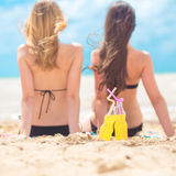 Deux amies se reposant sur la plage Photo stock