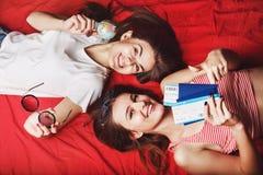 Deux amies se trouvant sur le lit rouge Photos libres de droits