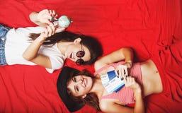 Deux amies se trouvant sur le lit rouge Image stock