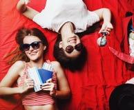 Deux amies se trouvant sur le lit rouge Photos stock