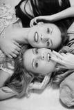 Deux amies sexy de charme s'étendant dans le lit ensemble Photos stock