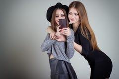 Deux amies sexy de sourire gaies de fille photographiées au téléphone, font le téléphone de selfie dans le studio sur un fond gri Photo stock