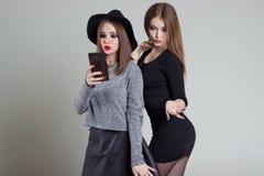 Deux amies sexy de sourire gaies de fille photographiées au téléphone, font le téléphone de selfie dans le studio sur un fond gri Photos libres de droits