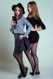 Deux amies sexy de sourire gaies de fille photographiées au téléphone, font le téléphone de selfie dans le studio sur un fond gri Images stock