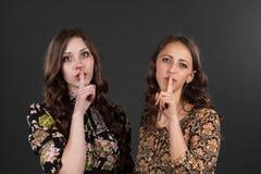 Deux amies sont invitées à être silencieuses, ne disent pas n'importe qui Image stock