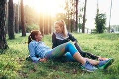 Deux amies sportives détendant, se trouvant sur l'herbe et causant dans la forêt après avoir pulsé ensemble Photographie stock