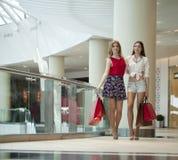 Deux amies sur des achats marchent au centre commercial avec des sacs Image libre de droits