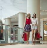 Deux amies sur des achats marchent au centre commercial avec des sacs Images stock