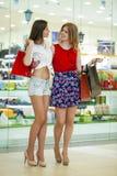 Deux amies sur des achats marchent au centre commercial avec des sacs Photos stock
