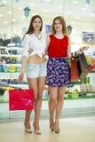 Deux amies sur des achats marchent au centre commercial avec des sacs Photo libre de droits